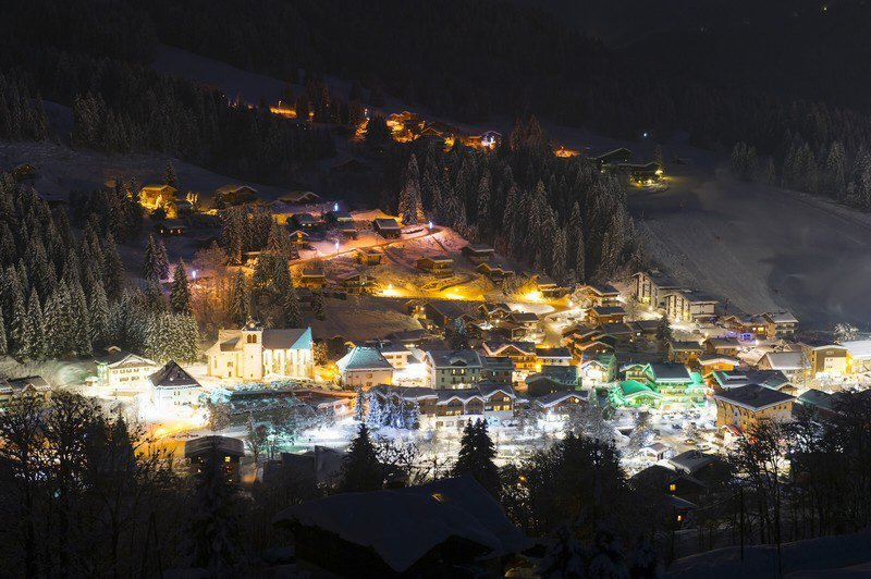View across Les Gets village at night showing the church and Rue du Centre